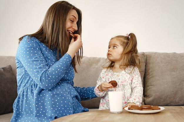 Mama w ciąży w sukience. dziewczyna pije mleko. mama i córka lubią ciasteczka.