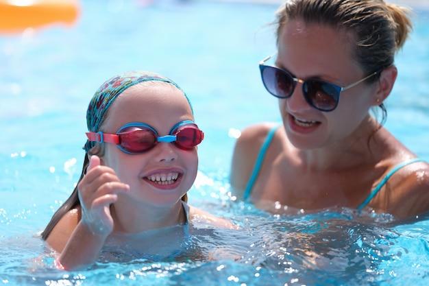 Mama w okularach przeciwsłonecznych uczy córkę pływania w basenie?