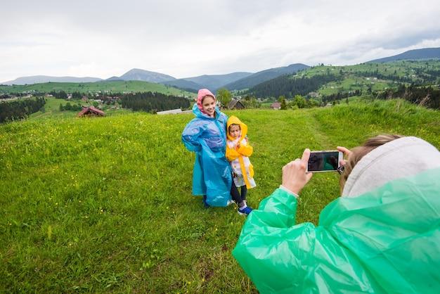 Mama w płaszczu przeciwdeszczowym robi zdjęcia dwóm ślicznym dzieciom w płaszczach na tle malowniczych łąk