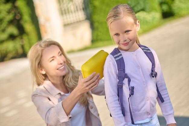 Mama wkłada lunchbox do plecaka dla małej córeczki