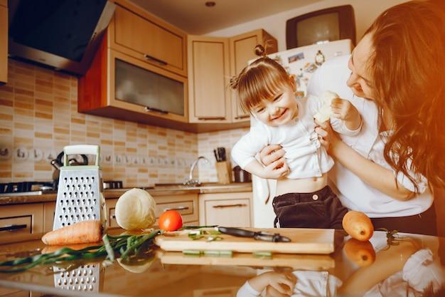 Mama wraz z córką gotuje warzywa w domu w kuchni