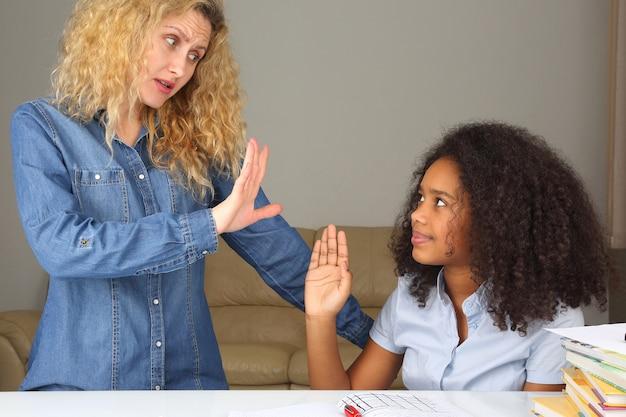 Mama wskazująca ręką podnosi córkę