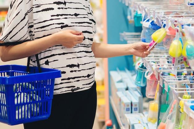 Mama wybiera produkt dla noworodka w supermarkecie. ciąża i zakupy.