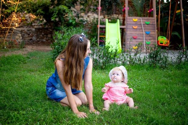Mama z córeczką na zielonym trawniku na placu zabaw latem bawi się