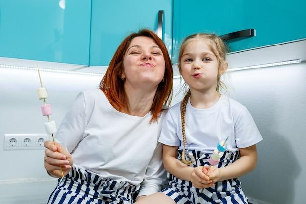 Mama z córką w turkusowej kuchni jedzą pianki. cudowne relacje rodzinne. koncepcja szczęśliwej rodziny, szczęśliwi rodzice i dzieci