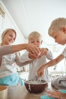 Mama z dwoma synami gotuje ciasto świąteczne w kuchni. życie codzienne