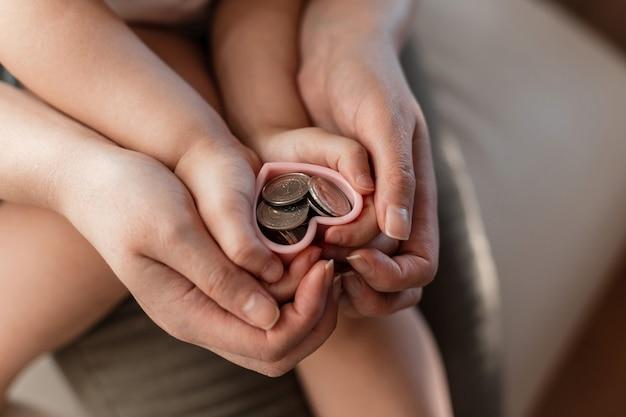 Mama z dzieckiem trzyma w rękach monety. zapisywanie koncepcji finansów. mama z córką wręcza serca pieniędzmi