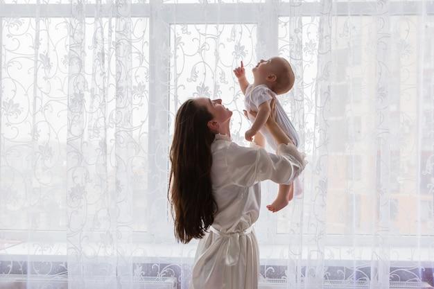 Mama z dzieckiem w pobliżu okna sypialni