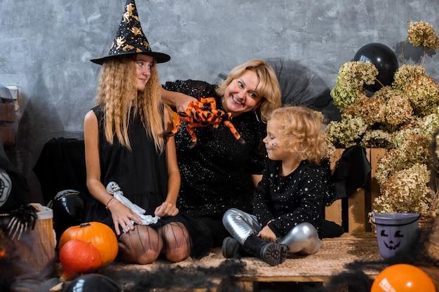 Mama z dziećmi dwie dziewczynki i córki wśród wystroju z pomarańczowymi i czarnymi odcieniami na halloween baw się i spędzaj czas