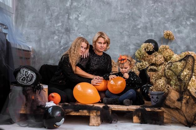 Mama z dziećmi dwie dziewczynki i córki wśród wystroju z pomarańczowymi i czarnymi odcieniami na halloween baw się i spędzaj