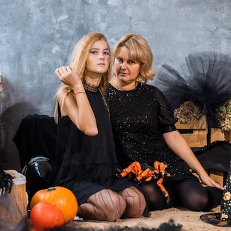 Mama z dziećmi dziewczynka córka 12 lat wśród wystroju z pomarańczowymi i czarnymi odcieniami na halloween baw się i spędzaj razem czas