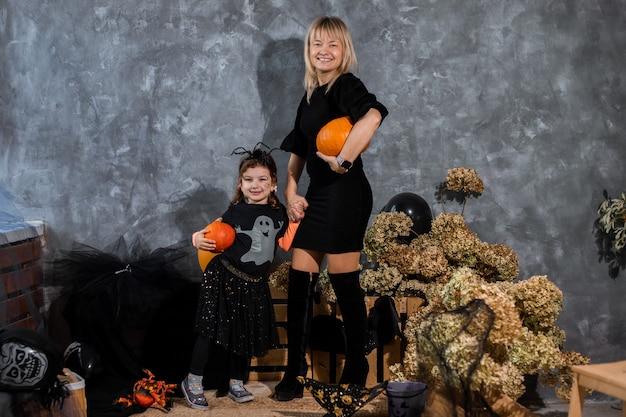 Mama z dziećmi dziewczynka córka 4 lata wśród wystroju z pomarańczowymi i czarnymi odcieniami na halloween baw się i spędzaj razem czas
