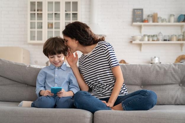 Mama z dziećmi na kanapie ogląda zabawne wideo na telefon komórkowy szepcząc do ucha, spędzając czas w domu.