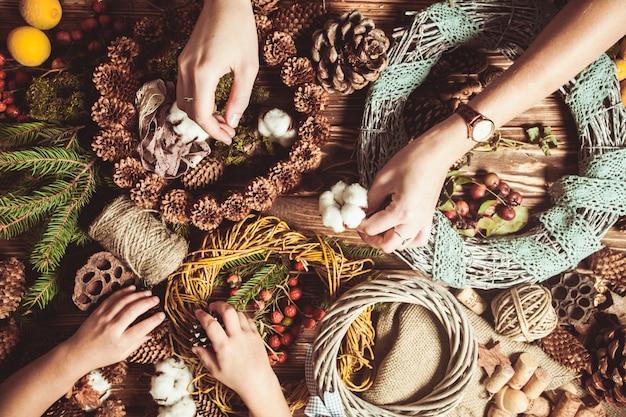 Mama z dziećmi robi naturalne wieńce świąteczne do dekoracji domu. stolik z widokiem z góry z rękami