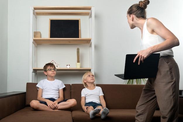 Mama z laptopem w rękach i dwóch chłopców na kanapie