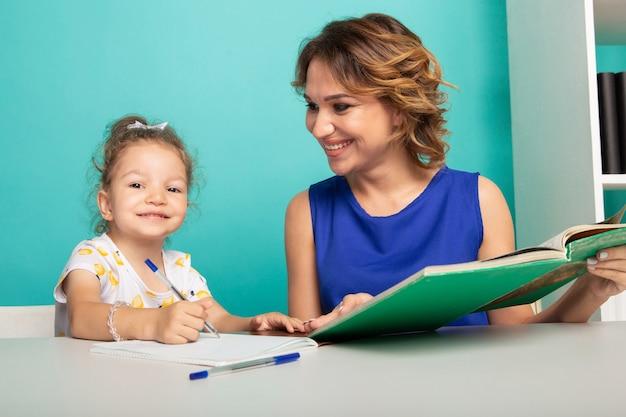 Mama z małą dziewczynką razem w domu siedzi przy stole