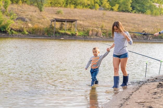 Mama z małym synkiem chodzi w gumowych butach po piaszczystym brzegu jeziora. spotykać się z dziećmi w naturze, z dala od miasta