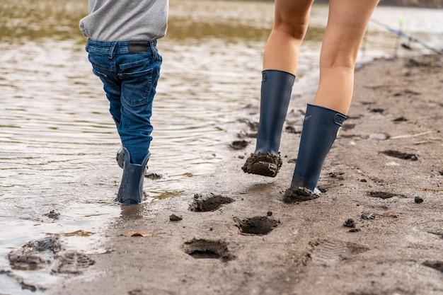 Mama z małym synkiem chodzi w gumowych butach wzdłuż piaszczystego brzegu jeziora. spotykać się z dziećmi w naturze, z dala od miasta
