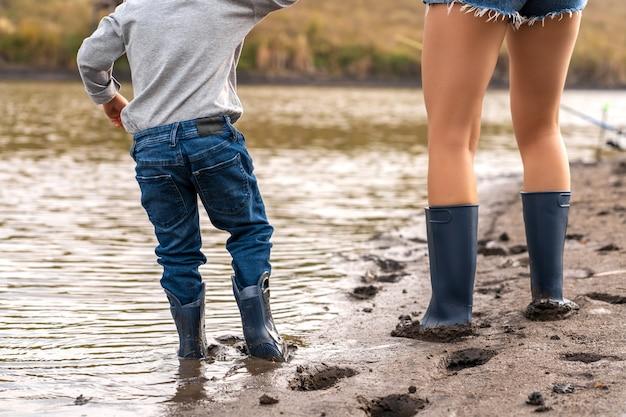 Mama z małym synkiem chodzi w gumowych butach wzdłuż piaszczystego brzegu jeziora