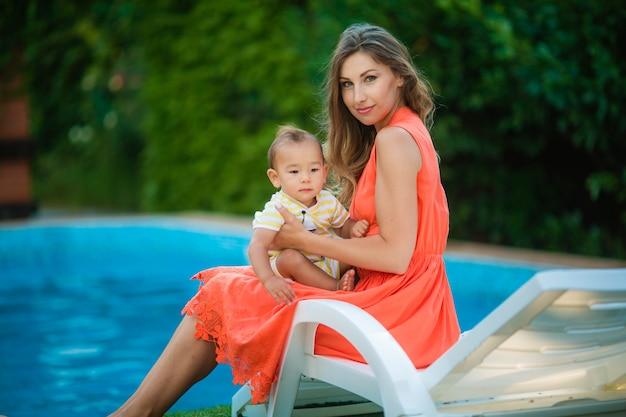 Mama z młodym synem na skraju basenu, siedząc na krześle do zabiegów słonecznych