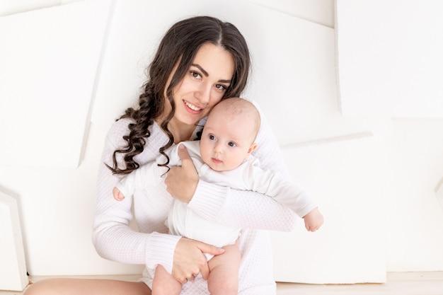 Mama z noworodkiem na rękach w domu, koncepcja szczęśliwej kochającej rodziny, dzień matki