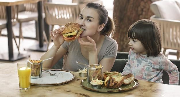 Mama z śliczną córką je fast food w kawiarni