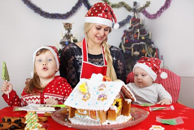 Mama z synem i córką dekorują piernikowy domek