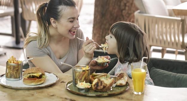 Mama z uroczą córką, jedzenie fast food w kawiarni