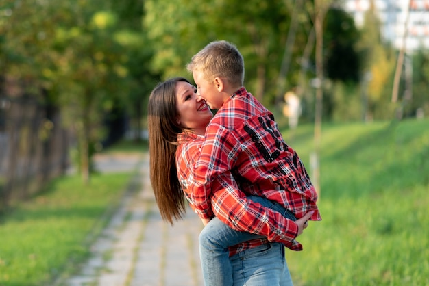 Mama z uśmiechem trzyma syna w ramionach. w dowolnym celu.