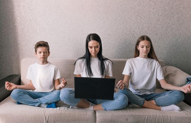 Mama z zapałem pracuje przy komputerze, dzieci siedząc obok siebie na kanapie rozmyślają nad koncepcją pracy i wypoczynku