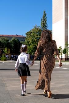 Mama zabiera córkę do pierwszej klasy szkoły