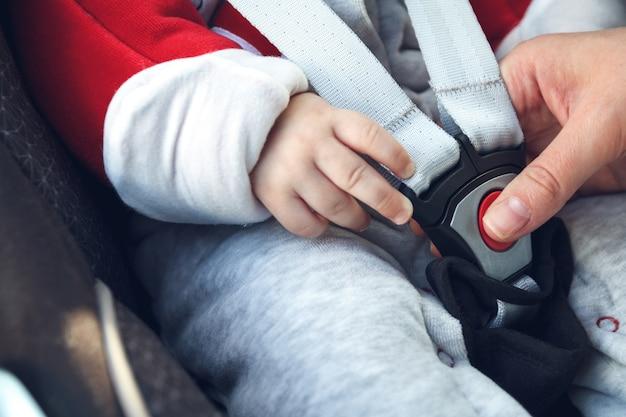 Mama zapina pas bezpieczeństwa w foteliku samochodowym, w którym siedzi jej małe dziecko