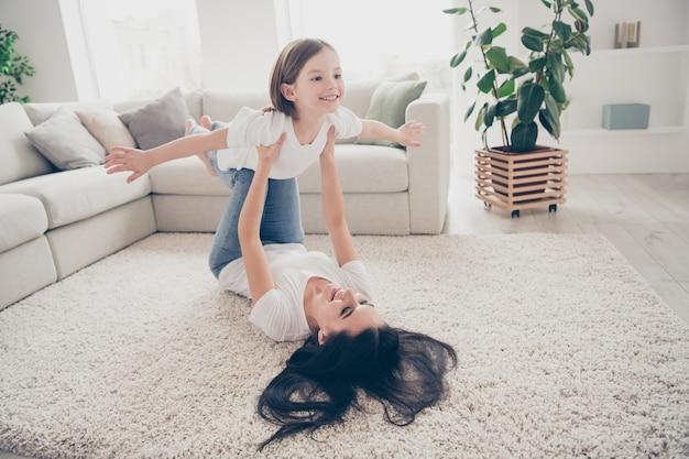 Mamusia nosi córkę, trzymając się za ręce jak samolot na dywanie w salonie