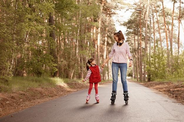 Mamusia z jej uroczą dziewczyną na rolkach w lesie