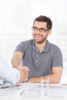 Mamy umowę. dwóch ludzi biznesu w swobodnym uścisku dłoni, podczas gdy jeden z nich się uśmiecha