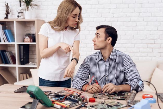 Man master repairing appliances w domu nd woman.