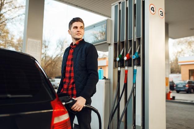Man tankuje pojazd na stacji benzynowej