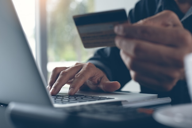 Man zakupy online i dokonywanie płatności internetowych za pośrednictwem laptopa