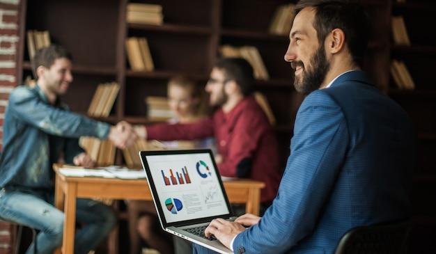 Manager finance pracuje z grafiką marketingową na laptopie w biurze