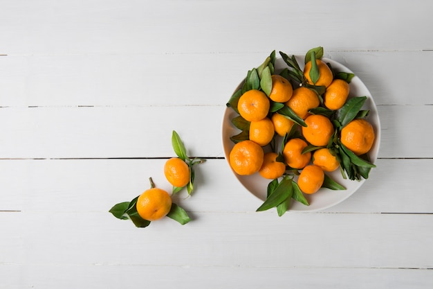 Mandaryn mandarynka z liśćmi w białym talerzu na białym drewnianym tle. widok z góry, kopia przestrzeń.