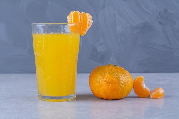 Mandarynka i szklanka soku pomarańczowego na marmurowym stole.