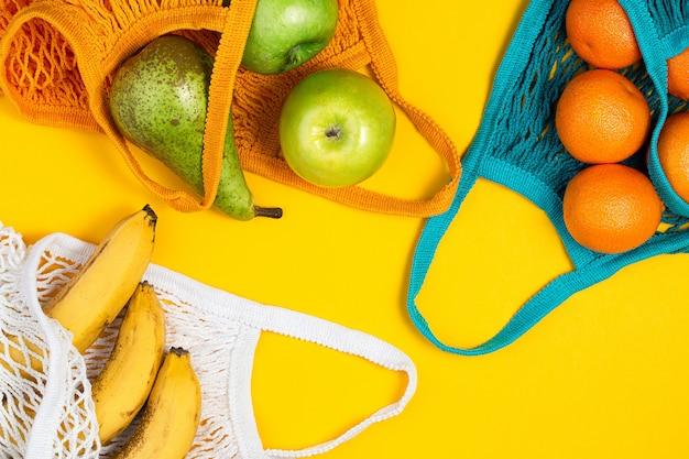 Mandarynki, banany i zielone jabłka w torbie smyczkowej na żółtym tle.