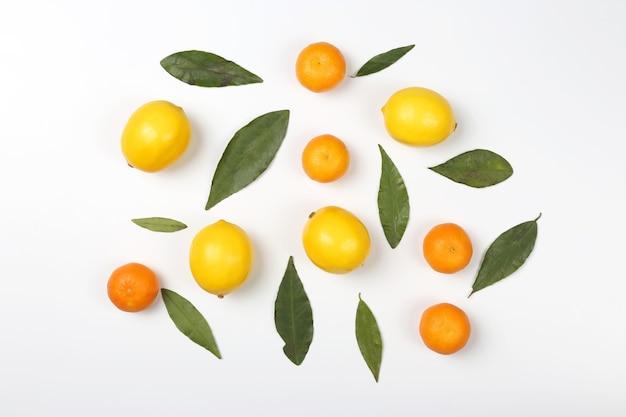 Mandarynki i cytryny z liśćmi na białym tle
