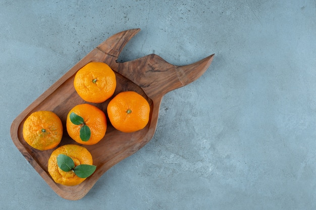 Mandarynki i pomarańcze na drewnianej tacy, na marmurowym stole.