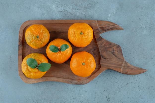 Mandarynki i pomarańcze na drewnianej tacy, na marmurowym tle.