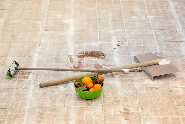 Mandarynki i pomarańcze w zielonej misce witaminy do pracy energia do pracy żelazna łopata i miotła