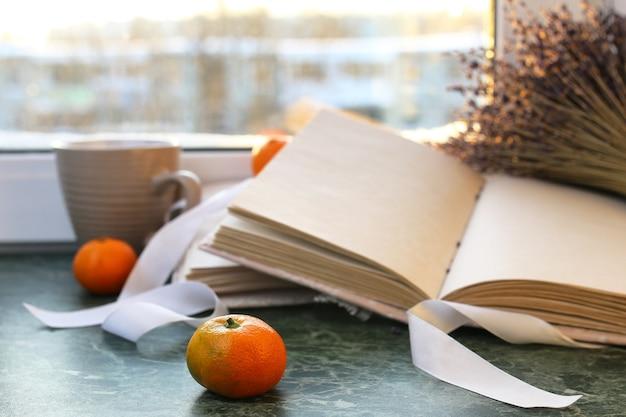 Mandarynki i zabytkowe książki na marmurowym stole przy oknie zimą