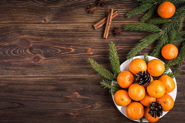 Mandarynki na drewnianych z gałęzi jodły boże narodzenie