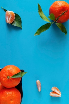 Mandarynki na niebieskiej powierzchni obok plasterków mandarynki.