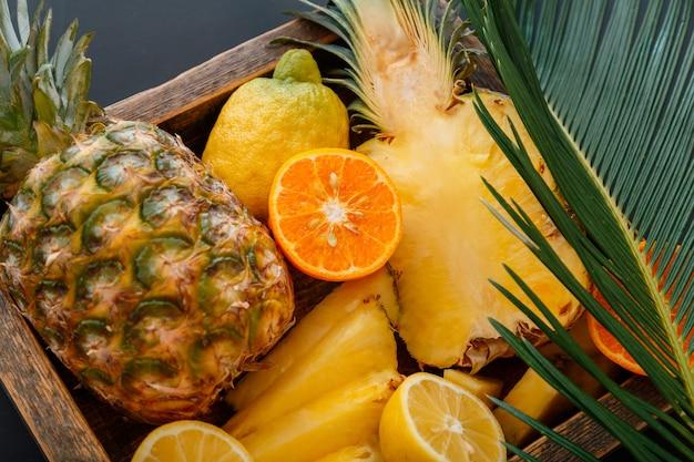 Mandarynki pomarańcze ananasy cytryny. wymieszaj pudełko z bukietem owoców tropikalnych i liści palmowych. tropikalny deser witaminowy jako tło lato. zdjęcie stockowe wysokiej jakości